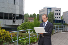 Businessman with white laptop standing outside Royalty Free Stock Images