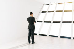 Businessman white room. Thinking businessman in white room with panoramic windows. 3D Rendering Stock Photo