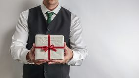 Businessman in suit vest holding a Christmas gift / present. Businessman in white shirt and black suit vest holding a Christmas gift / present. Copy space for royalty free stock photos