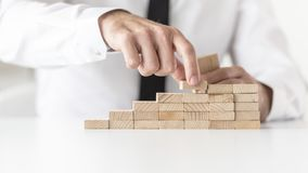 Businessman in white shirt building a graph or ladder of success Stock Photos