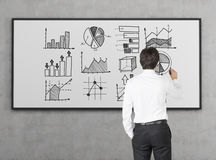 Businessman in white shirt is drawing diagrams on whiteboard. Rear view of businessman in white shirt drawing graphs on whiteboard. Concept of stats and big data Stock Photography