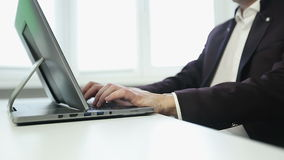 Businessman in white shirt and jacket is typing on a laptop in the office. Business concept stock video