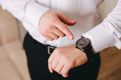Businessman in white shirt looking at his swiss wristwatch on his hand and watching the time Royalty Free Stock Photography