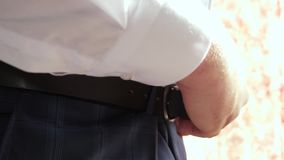 Businessman in white shirt puts belt on his pants. close-up. man gets dressed for work in the morning. office worker