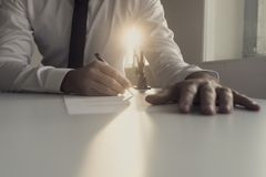 Businessman in white shirt signing document backlit by a shaft o. F bright sunlight in a low angle view of his hands stock images