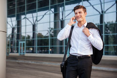 Businessman in white shirt talking on cell phone outdoors. Portrait of happy young handsome businessman in white shirt talking on cell phone outdoors Royalty Free Stock Photography
