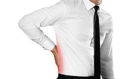 Businessman in a white shirt and tie holding his back. Back pain stock photos