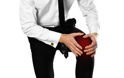 Businessman in a white shirt and tie holding his leg. Knee pain stock images