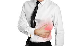 Businessman in a white shirt and tie holding his side. Pain in t stock photo