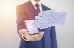 Businessman with smartphone with envelopes coming out of the screen Royalty Free Stock Photos