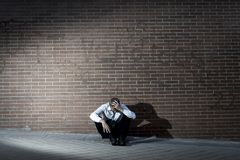 Businessman who lost job lost in depression sitting on city street corner Royalty Free Stock Photo