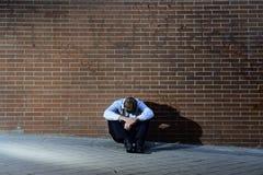 Businessman who lost job lost in depression sitting on city street corner Stock Photo