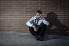 Businessman who lost job lost in depression sitting on city street corner Stock Photos