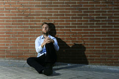 Businessman who lost job lost in depression sitting on city street corner Stock Images