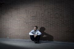 Businessman who lost job lost in depression sitting on city street corner Royalty Free Stock Images