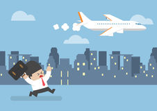 Businessman who missed his flight running behind a plane Royalty Free Stock Photo