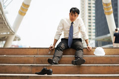 Businessman who are tired or stressed sit on the stairs. After working on the building background Stock Images