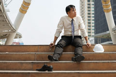Businessman who are tired or stressed sitting alone on stairs. Businessman who are tired or stressed sitting alone on the stairs after working on the building Royalty Free Stock Photo
