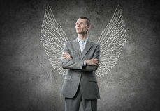 Businessman with wings. Young businessman with chalk drawn wings behind his back Royalty Free Stock Images