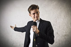 Businessman winking and holding a microphone Stock Photos
