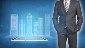 Businessman and wire-frame buildings on screen Stock Photography