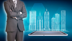Businessman and wire-frame buildings on screen Stock Photo