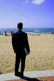 Businessman Wishing He wasn't. Man in suit looking at the beach Stock Images