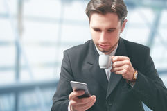 Businessman With Mobile Phone And Coffee Cup Royalty Free Stock Image