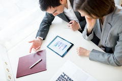 A businessman and woman brainstorming. High angle view of a young businessman and women having a brainstorming session as they sit together at a desk in the Royalty Free Stock Image