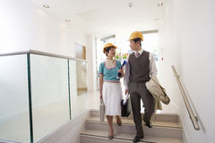 Businessman and woman with briefcases in hard hats on stairs, looking at each other Royalty Free Stock Image