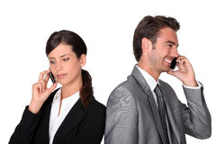 Businessman and woman with cellphones Royalty Free Stock Image