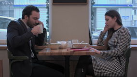 Businessman and woman communicate by smartphones at lunch in cafe stock video