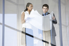 A businessman and woman discussing plans or blueprints Stock Photo