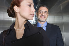 Businessman and woman in elevator, close-up stock photo