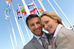 Businessman and woman with flags. Stock Photos