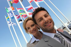 Businessman and woman by flags Stock Photos