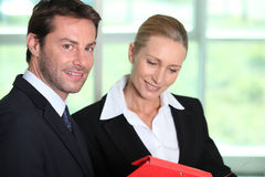 Businessman and woman with folder. Businessman and women looking at folder Stock Photography