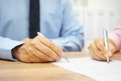 Businessman and woman hand signing agreement in office Stock Image