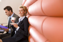 Businessman and woman having meeting in booth in cafe, woman with coffee cup, smiling, portrait Stock Photos