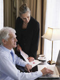 Businessman And Woman With Laptop And Documents Stock Photo