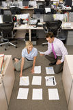 Businessman and woman organising paperwork into piles on floor, elevated view Stock Image
