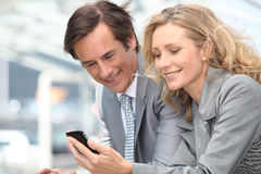 Businessman and woman with phone Royalty Free Stock Image
