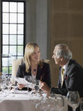 Businessman And Woman Reading Documents At Restaurant Table Stock Images