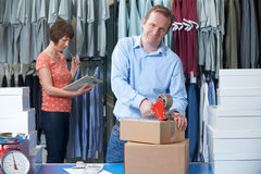 Businessman And Woman Running Online Clothing Company. Couple Running Online Clothing Store From Warehouse Royalty Free Stock Photo