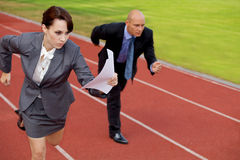 Businessman and woman on running on race track Stock Images