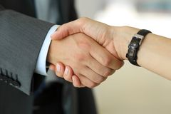 Businessman and woman shake hands as hello in office closeup Royalty Free Stock Photo