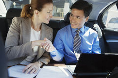 Businessman and woman shaking hands in the back-seat of car, man using laptop, woman with contract Royalty Free Stock Photo