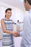 Businessman and woman shaking hands in foyer, smiling, close-up Stock Photo