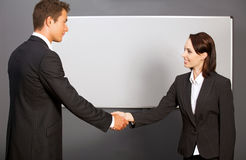 Businessman and woman shaking hands in office, smiling Royalty Free Stock Image