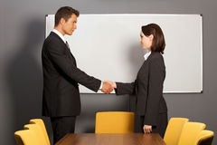 Businessman and woman shaking hands in office, smiling Royalty Free Stock Photos